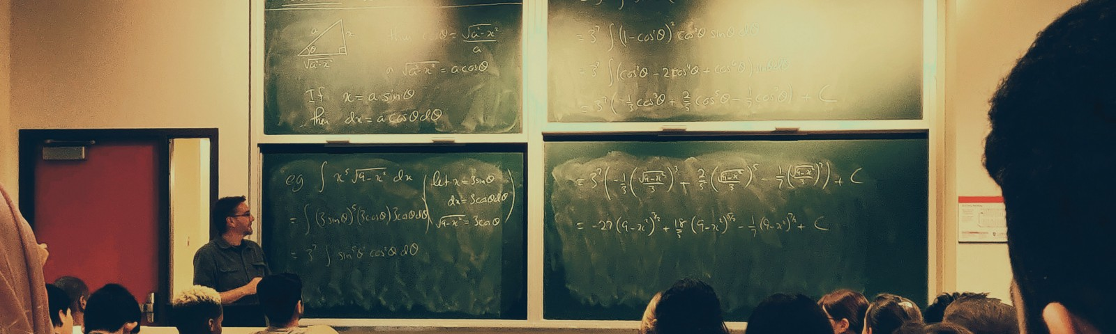 Students sit in a class with algebra on the chalkboard