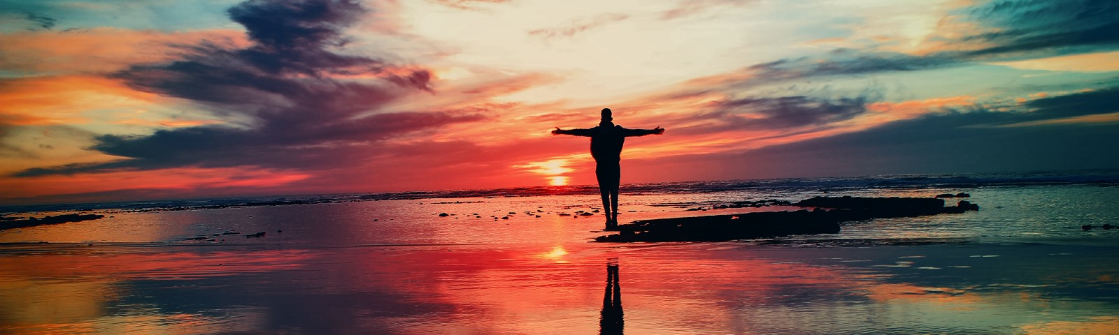 A silhouetted figure stands with arms outstretched against a striking blue/red sunset backdrop with reflective sandy ground.