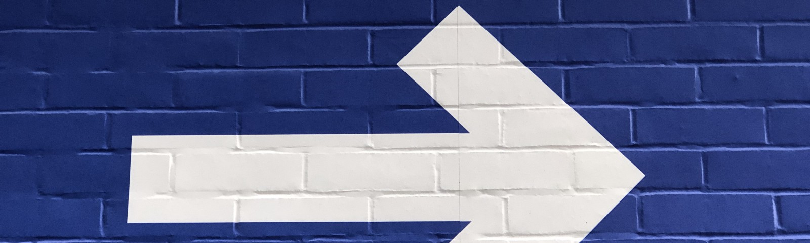white right-pointing painted on blue wall
