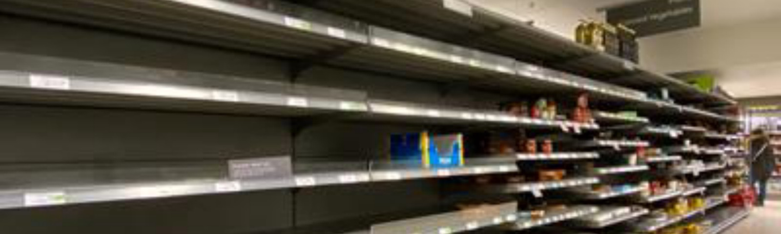 Picture of largely empty supermarket shelving with a few empty product boxes lying untidily in the shelves.