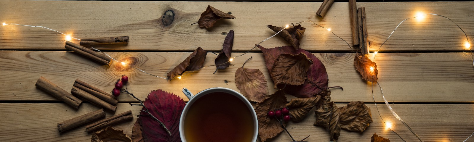 A cup of tea on a wood table, surrounded by dried leaves, sticks, and lights on a string