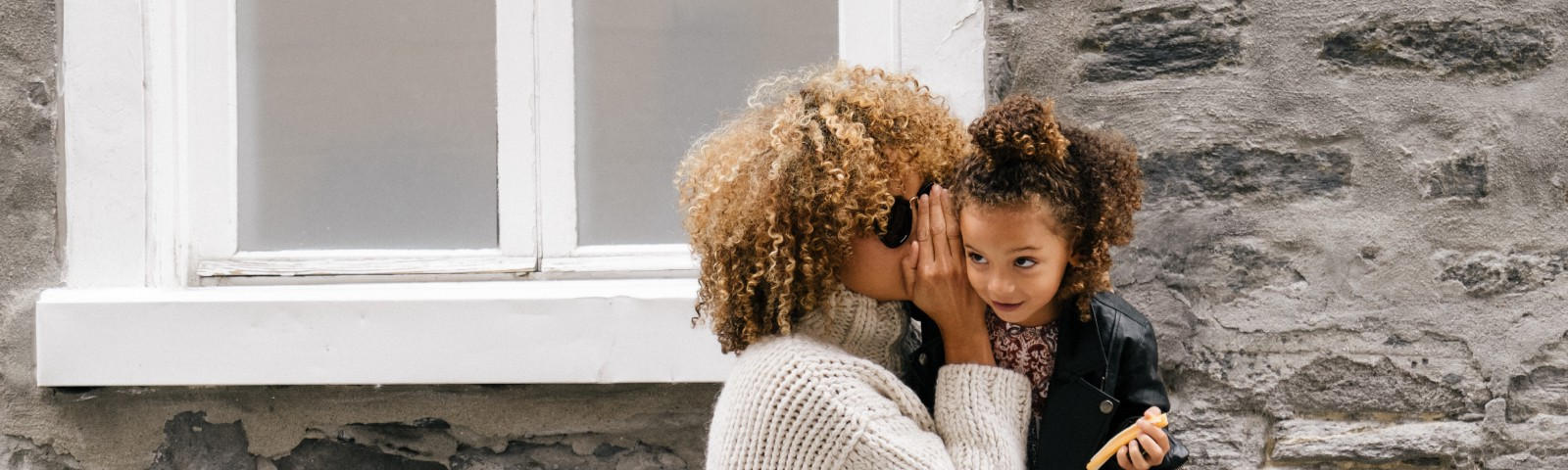 Mother whispering into a child's ear outside a house