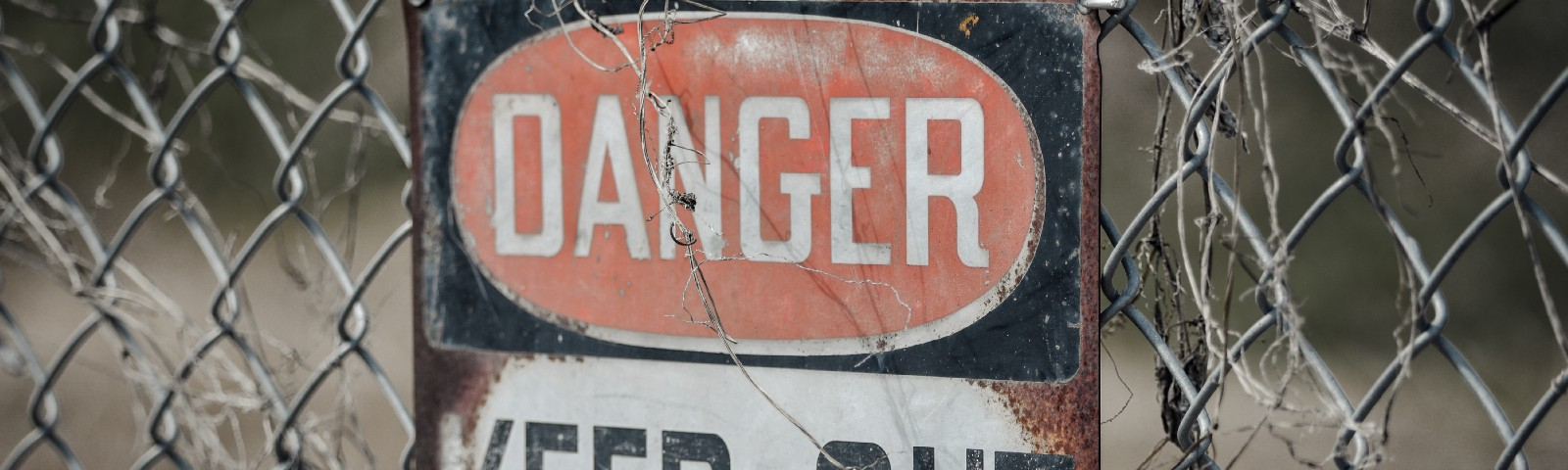 A sign on a fence: Danger Keep Out