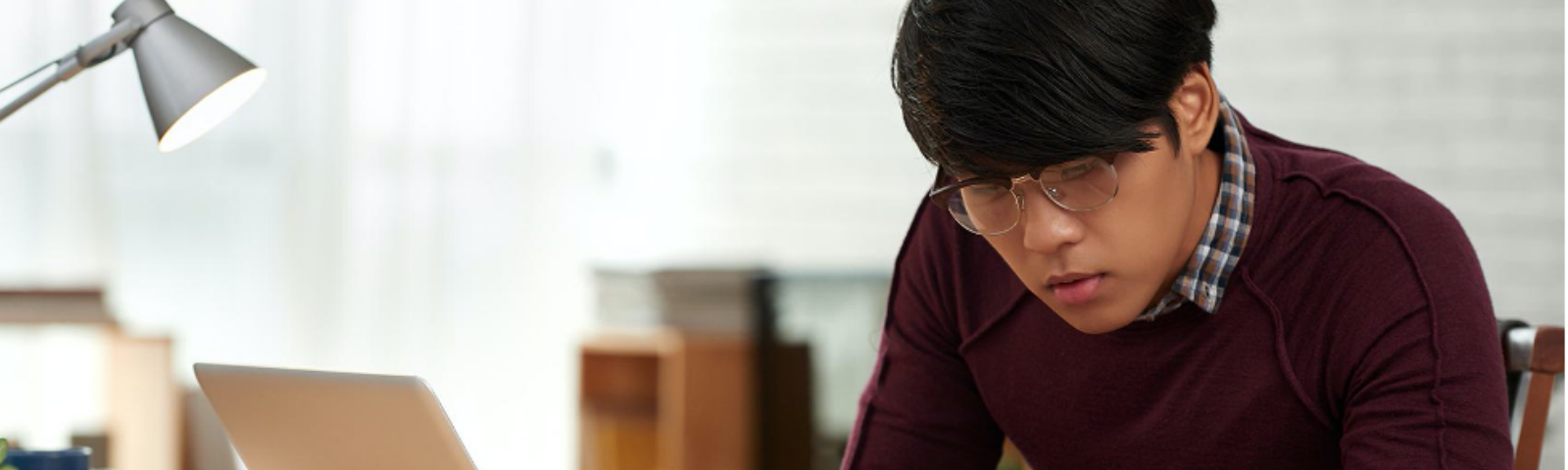 Young engineer wearing glasses and maroon sweater studying at computer