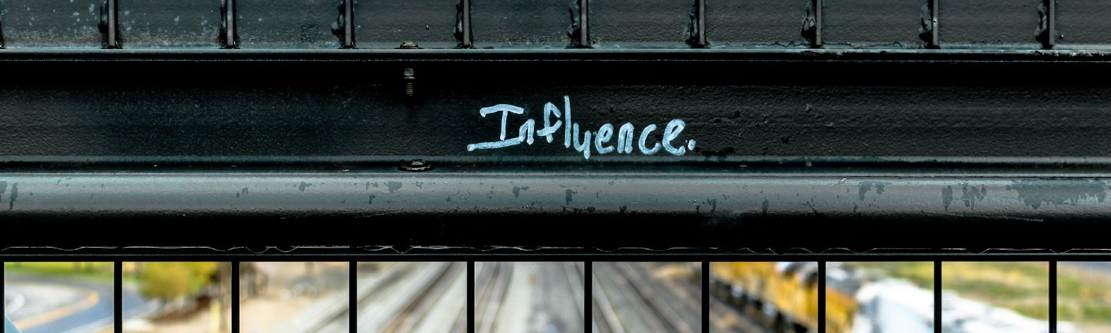 """A bridge overlooking railroad tracks with the word """"Influence"""" written on a guard rail"""
