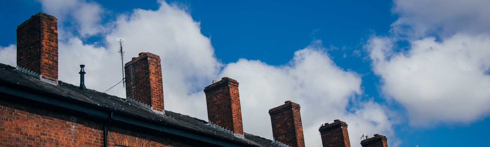 A row of brick-built terraced houses under a bright blue sky with a few white clouds.