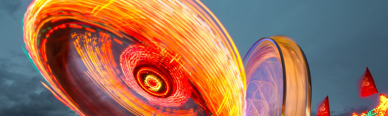 two Ferris wheels photographed with a slow shutter speed to produce a blur of lights