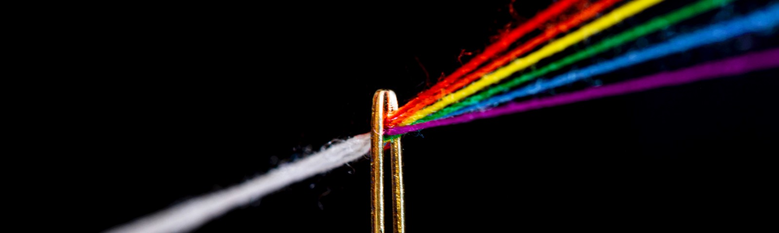 a white thread drawn through the eye of a needle turns into threads in all of the colors of the rainbow