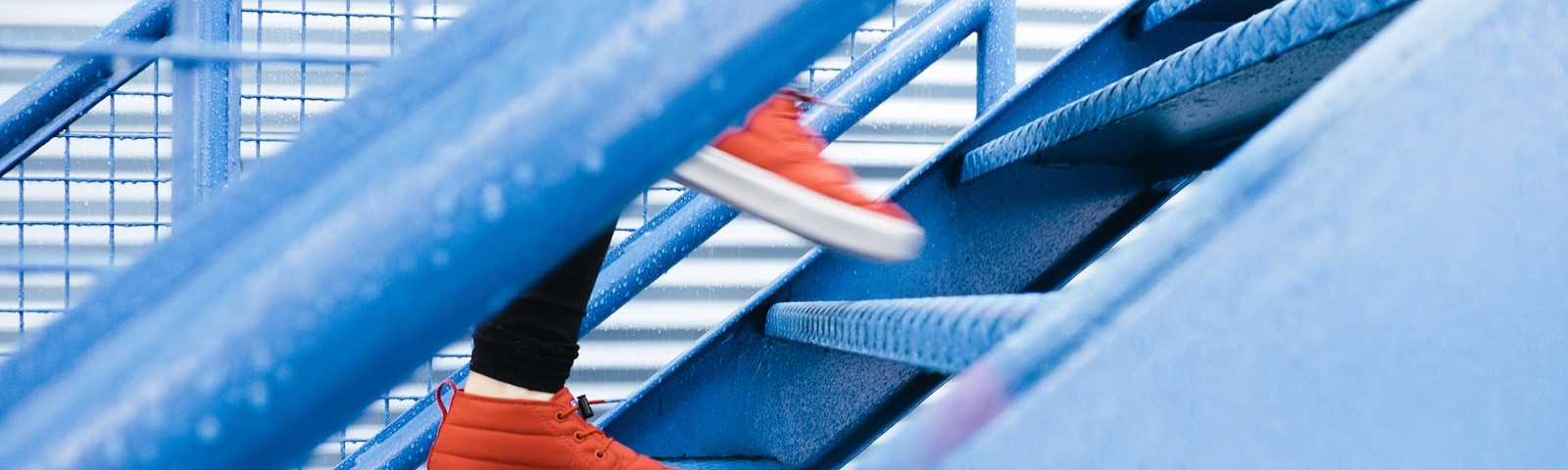 Red sneakers walking swiftly up a blue-tinged metallic staircase.