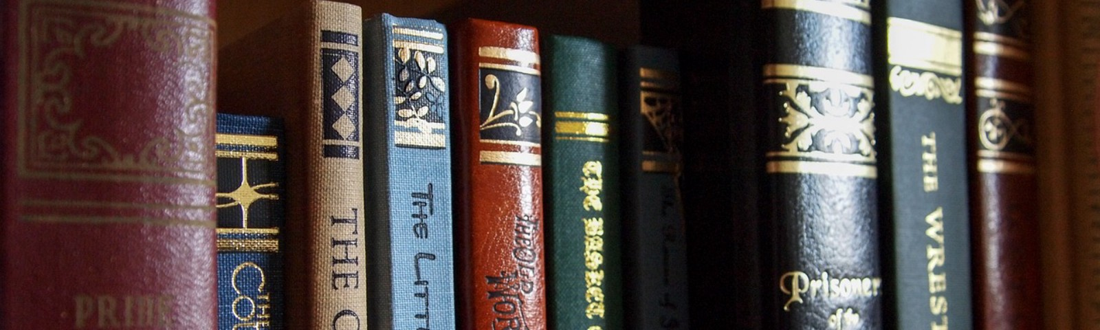 A close up of well kept older hardback books on a bookshelf.