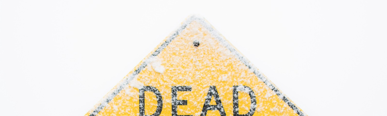 A dead end sign covered in snow.