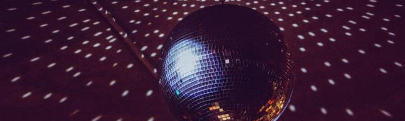 A disco ball reflects on the ceiling of a dark room.