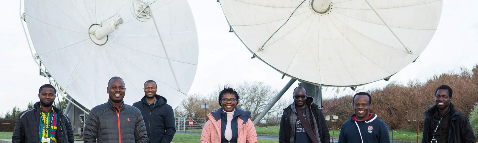 Seven students from the DARA training programme in a field with radio telescopes behind, at Goonhilly Station in Cornwall