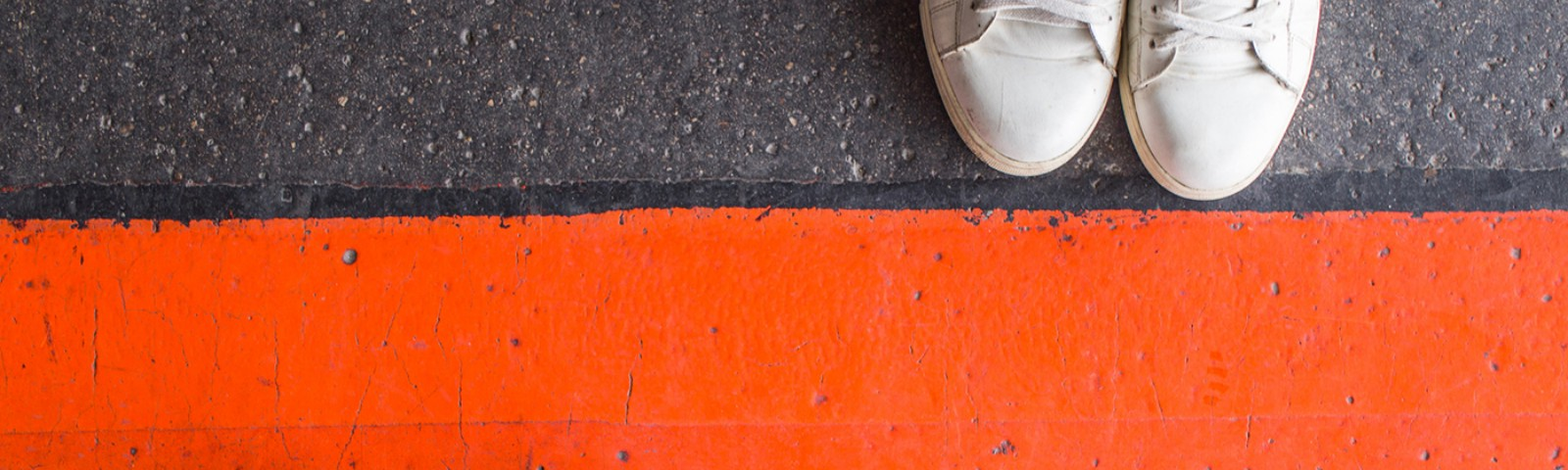 Two sets of feet, one in brown shoes, the other in white shoes, are separated by an orange line