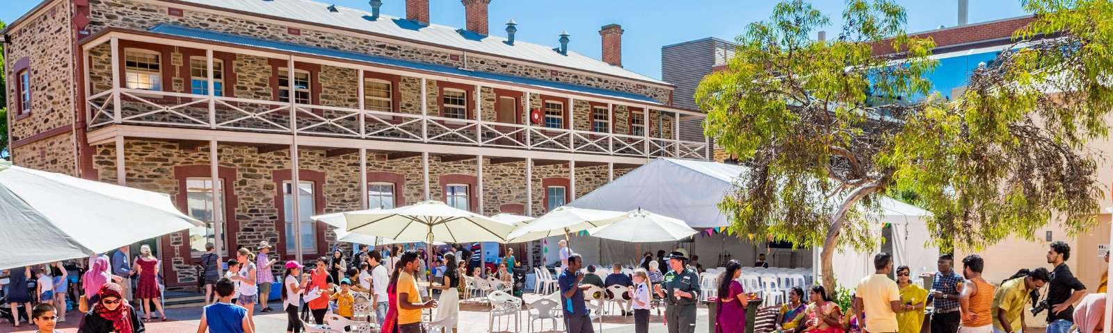 Crowd of people in a courtyard with marquee and umbrellas set up in front of a two story bluestone building.