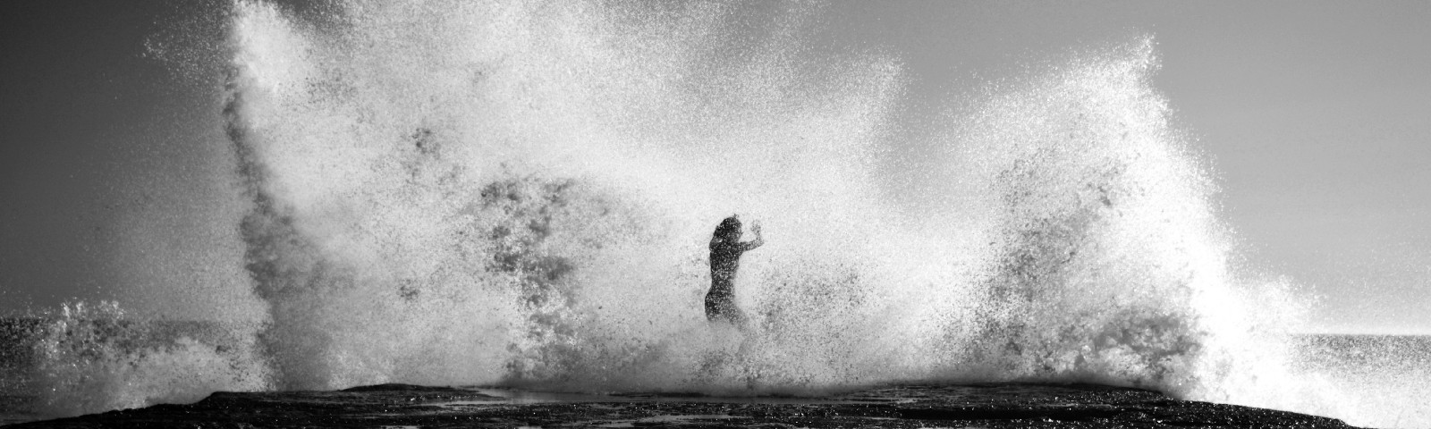 Gigantic wave crashing over person, black and white, nostalgic feel