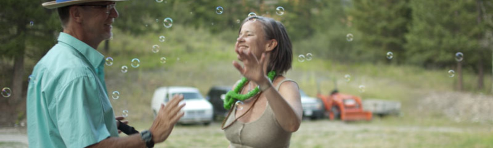 A white man and white woman standing in a field playing with bubbles