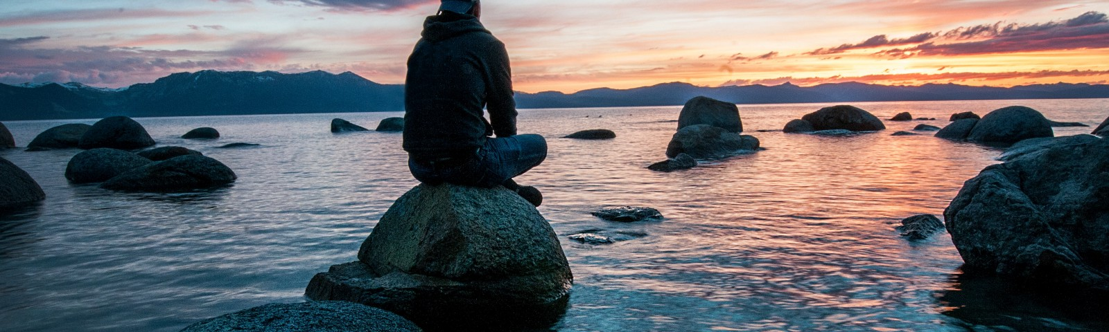 Guy sitting on a rock in an ocean cove looking out over the sun setting.