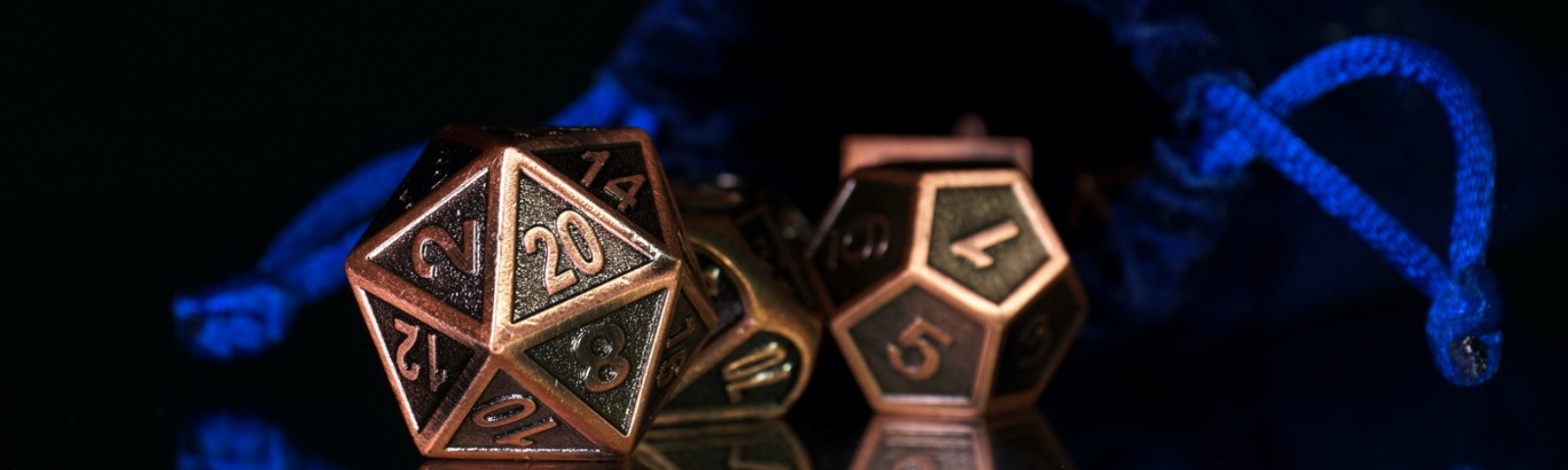 A copper d20 and d12 against a dark background.