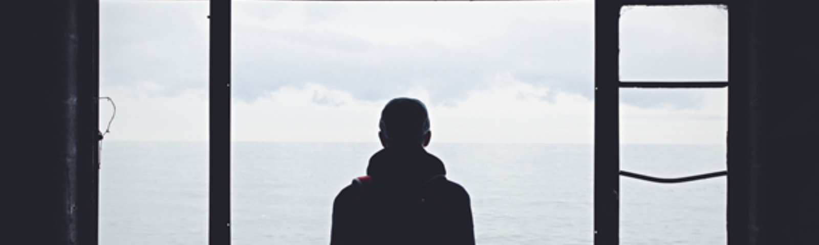 Man looking out of window at the sea, alone