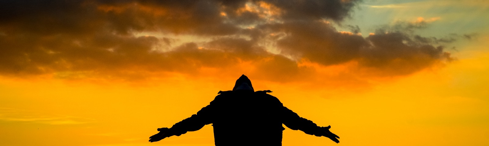 A man standing with arms outstretched, head back, in front of a beautiful sunset