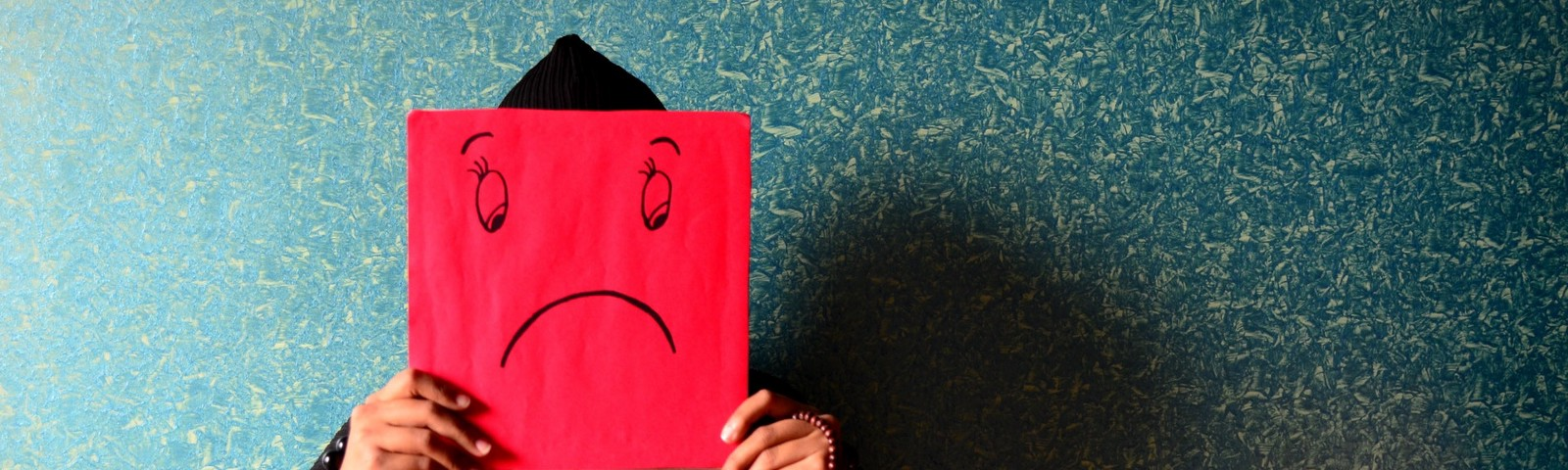 A person sitting in front an interior wall, holding a red sign with a sad smiley in front of their face.