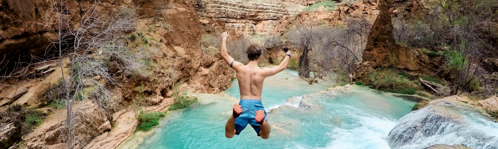 Topless Man Jumping on Body of Water