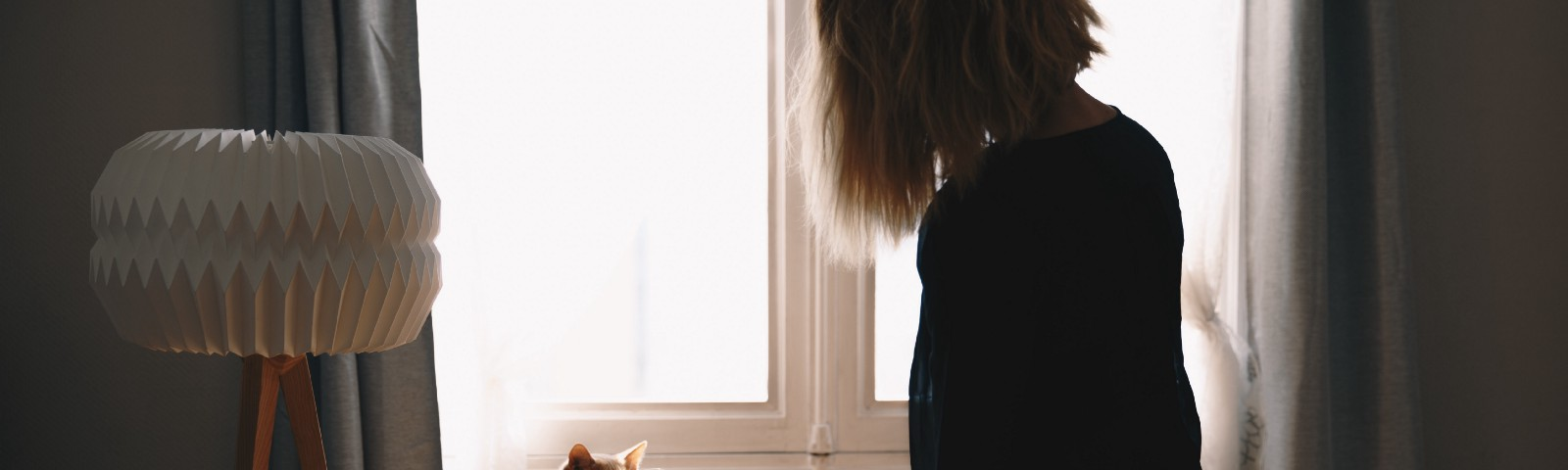 A girl sits on a table looking out the window with her orange cat beside her looking at her. Her back is to the viewer.