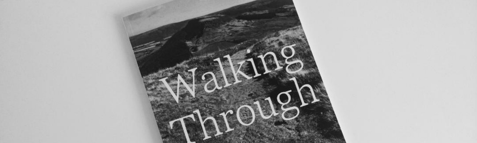 """Poetry collection called """"Walking Through"""" by Chris Bridge. On the book is a photo of countryside."""