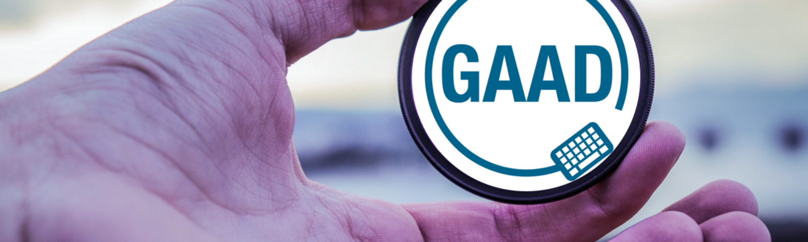 Man holding a lens, with the Global Accessibility Awareness Day logo added.