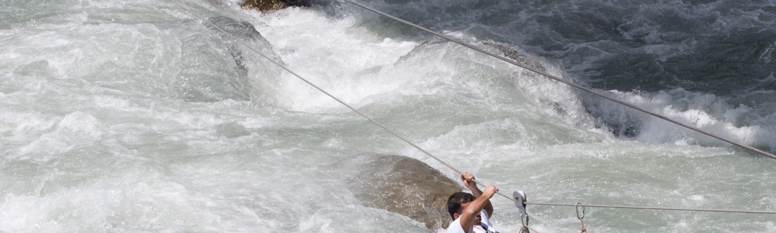 Man crossing a river pulling himself over a rope