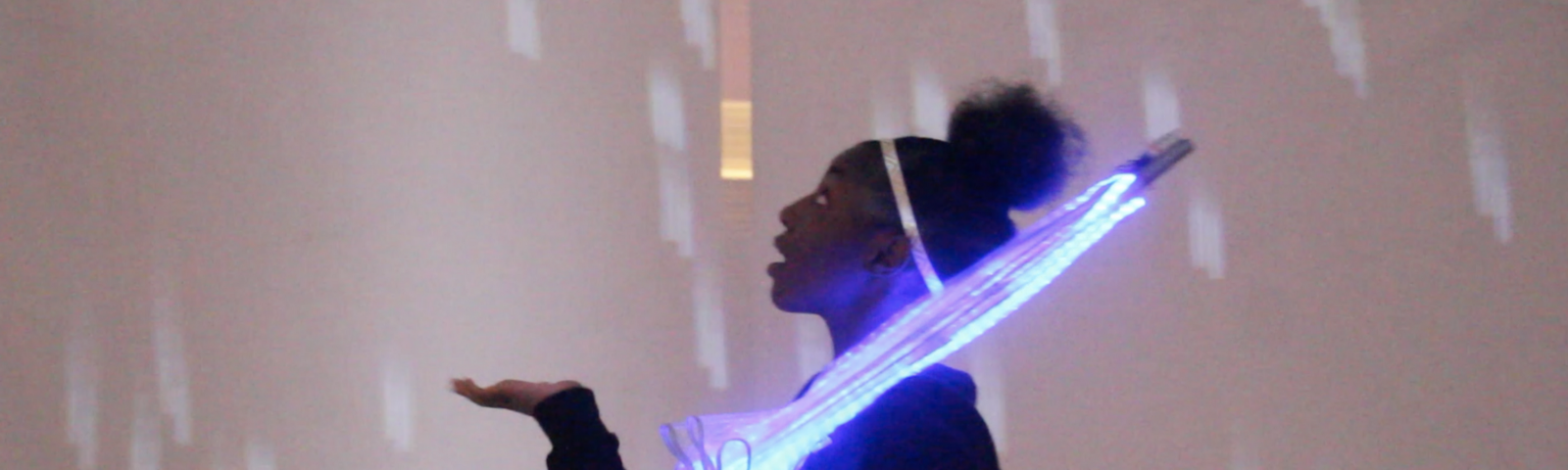 A young girl holds an illuminated umbrella. She holds out her hand and looks up at digital rain.