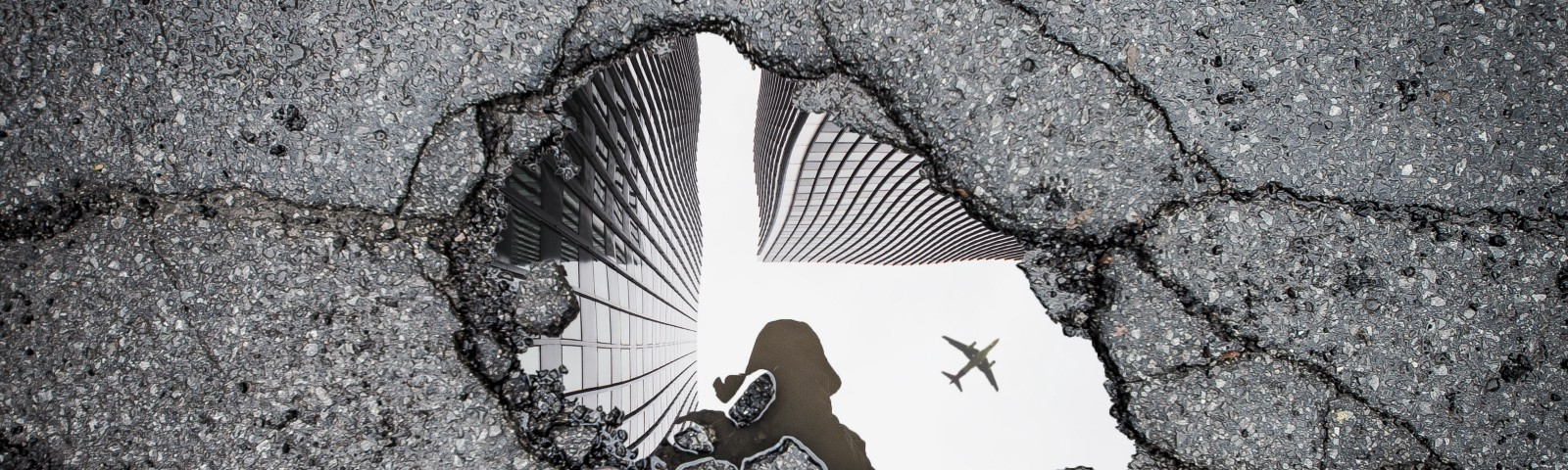 Image of a puddle reflecting skyscrapers and an airplane
