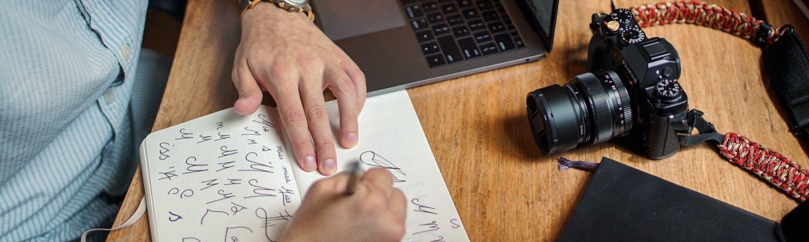 man writing on paper in front of dslr camera