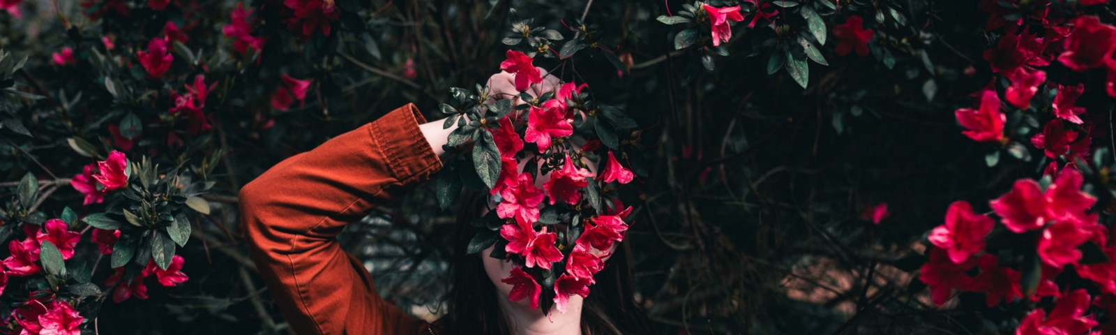 Woman holding a bunch of flowers obscuring her face