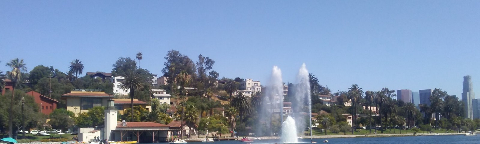 Echo Park Lake fountain, boat concourse and homes on the hillside.
