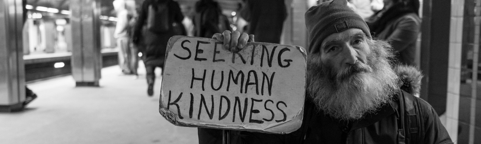 "Homeless man holding up a sign that says ""Seeking human kindness"""