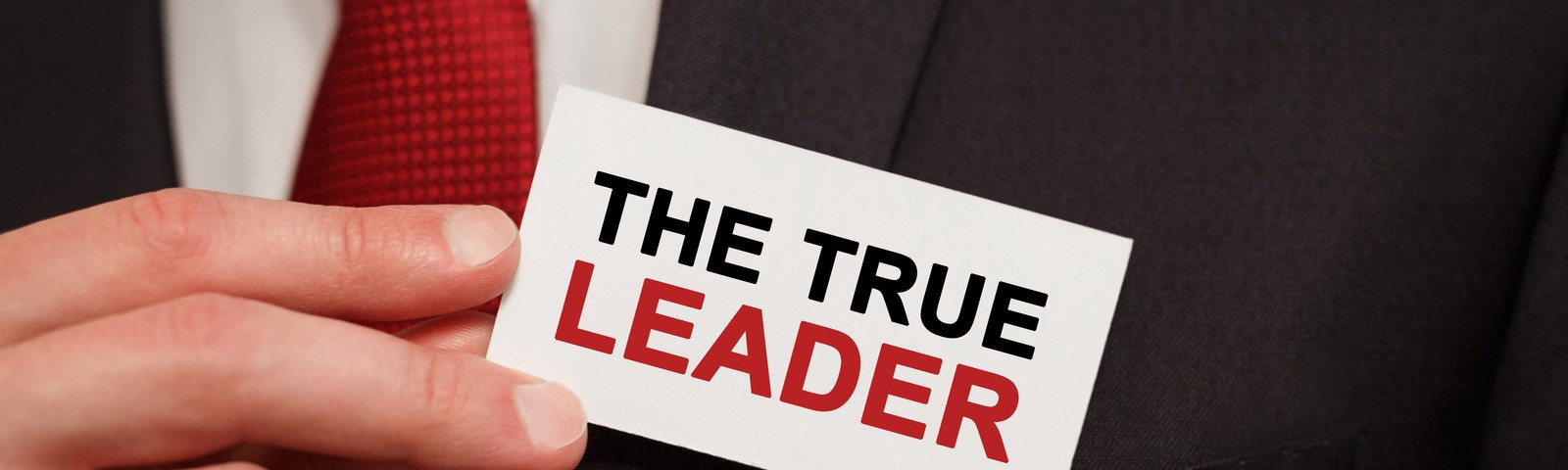 """Man pulling a card that says """"the true leader"""" out of breast pocket"""