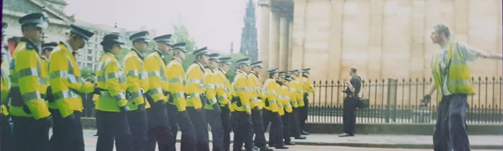 A lone reclaim the streets supporter stands defiant against a row of police officers. The mound, Edinburgh 2000/2001