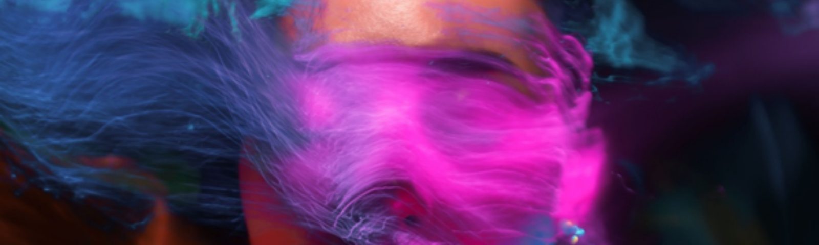 Photo by Sergey Katyshkin from Pexels showing a face mostly obscured by vibrant airbrushed colors of pinks, purples, oranges and blues.