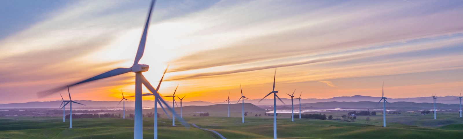 Windfarm windmills on green rolling hills against a sunset.