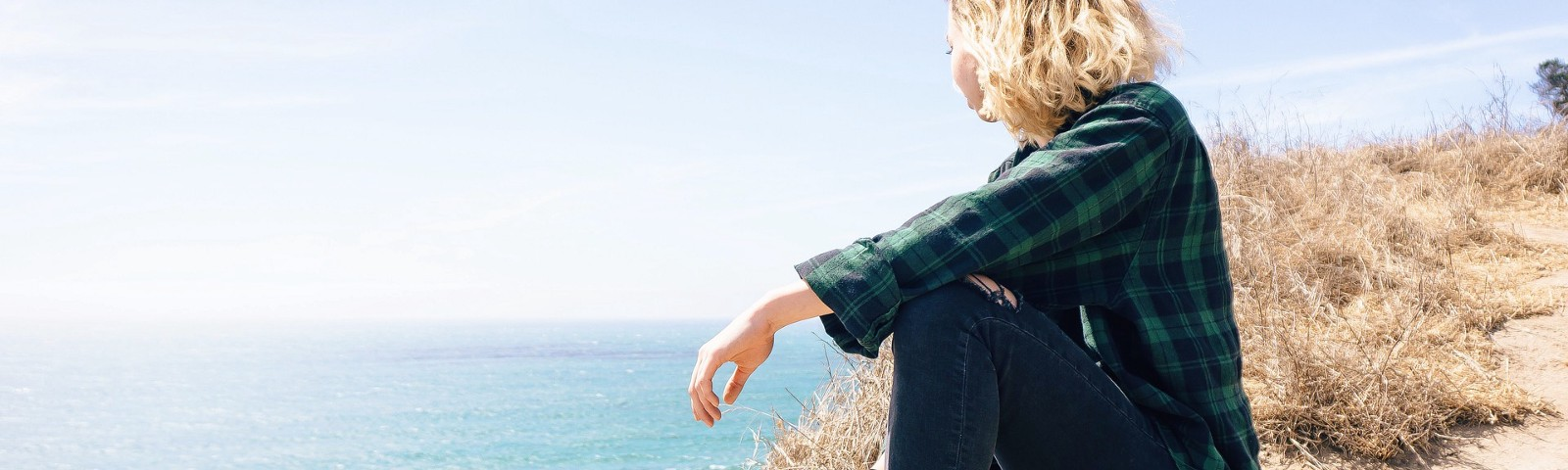 blond woman sitting on a cliff overlooking the ocean imagining her dreams coming true