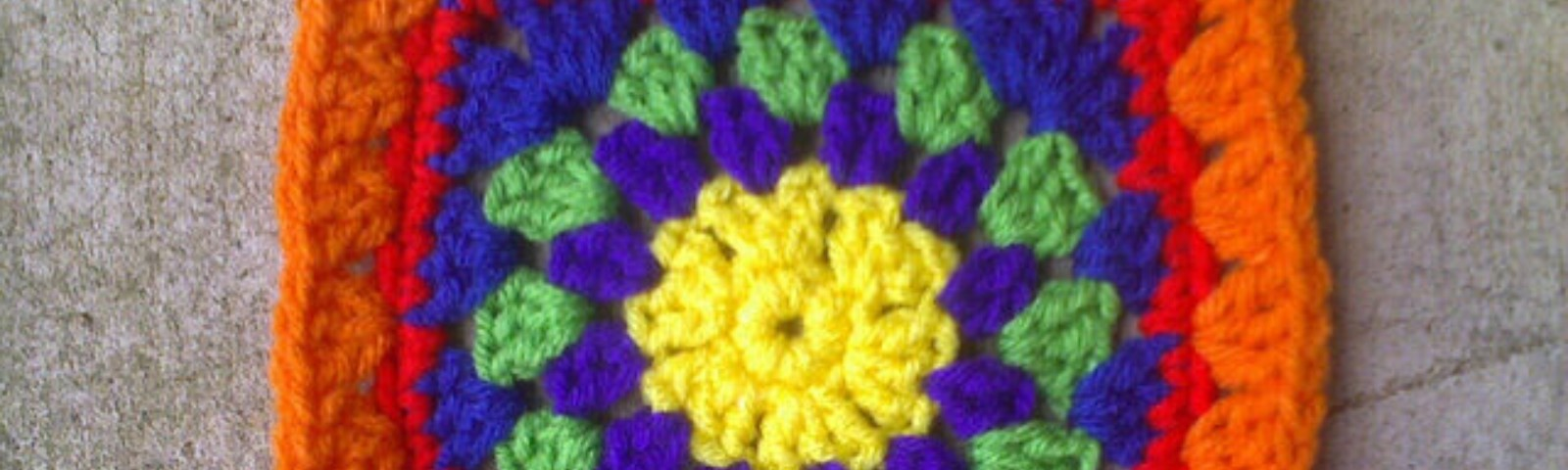 A multi color granny square that starts with a crochet circle in the center, but is squared off by the seventh round