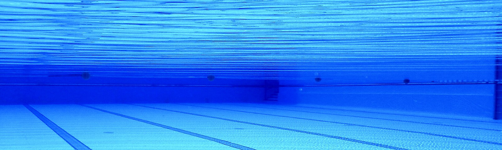 Underwater photo of a blue pool with lane markings on the bottom.