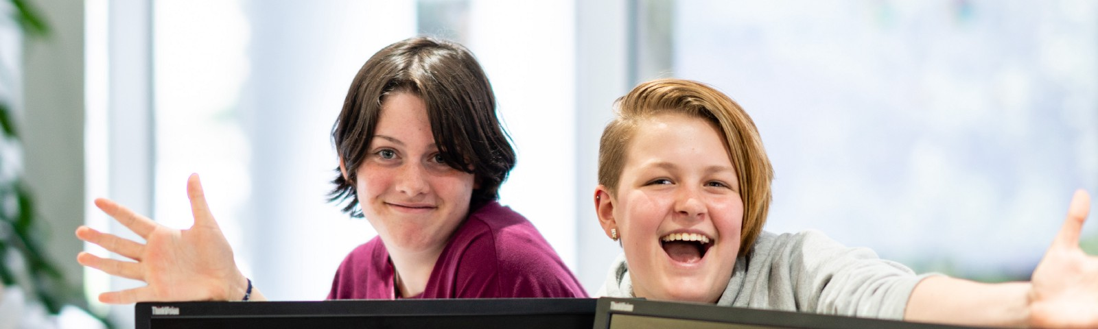 Two young people with their hands out smiling behind two laptop monitors