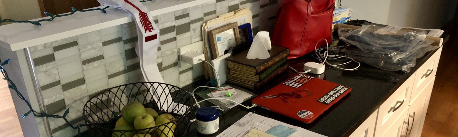 Author's photo of a kitchen counter with piles of papers, a laptop, red purse, basket of apples