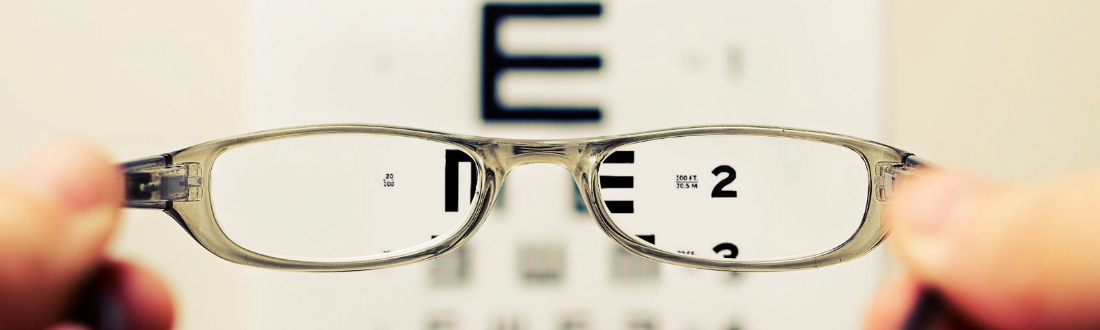Person holding glasses in front of an optometrists eye chart