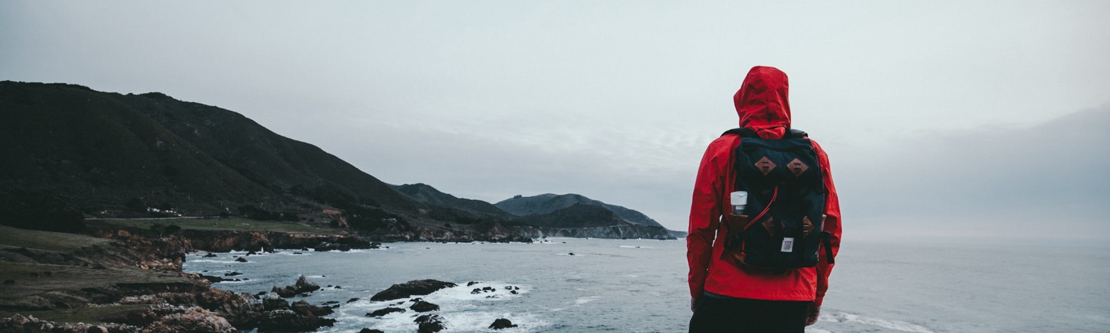 7 Powerful Life Lessons From Living Out of 2 Backpacks For Years—man with red jacket standing on lake