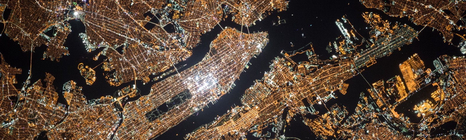 Overhead night view of New York city, glowing copper around black waterways and greenbelts.