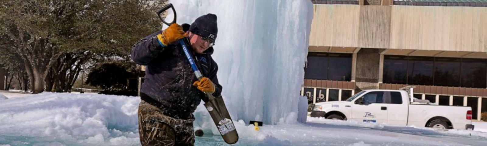 City Worker Breaks up ice in a water fountain inside it.